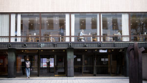 Porthania-byggnaden som tillhör Helsingfors universitet. Vid fönstret kan man se några enstaka människor äta lunch.