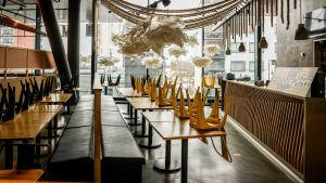 Stolar har placerats upp och ner på borden i en restauranglokal.