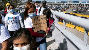 Migranter håller upp plakat och vädjar till Joe Biden om att få komma in till USA.