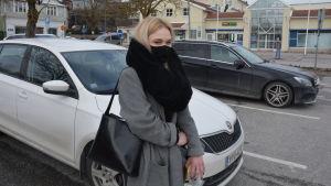 Ljushårig kvinna på parkering.