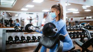 En kvinna i munskydd sitter och lyfter vikter på ett gym.