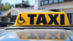 En gul taxiskylt ovanpå en bil.