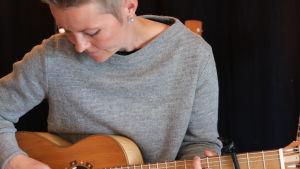 Désirée Saarela med gitarri famnen, tittar ner.