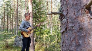 I förgrunden en granstamm, i bakgrunden kvinna med gitarr.