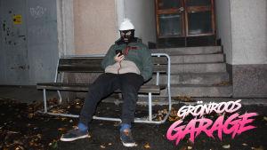 Finska snubben i skidluva sitter utomhus på bänk framför en betongbyggnads trappa och scrollar på sin telefon.