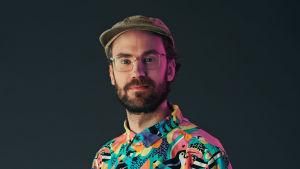 porträttbild av axel brink. han bär en färgrann skjorta med djungeldjur på och har skägg och glasögon och keps