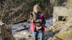 En kvinna med en hund i famnen framför en fors.
