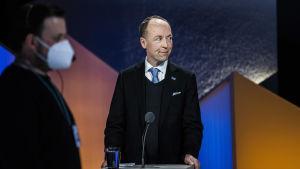 TIll vänster en man i profil som har munskydd, till höger en man i kostym med en mikrofon framför sig.
