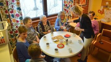 En dam häller i kaffe i koppar på ett bord. Runt bordet sitter sex andra damer.