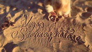 Barn leker med stenar på sandstrand, i sanden står skrivet Vegas sommarpratare