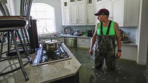 En man inspekterar översvämningarna i sitt kök.