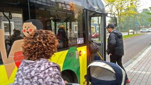 Passagerare stiger på buss.