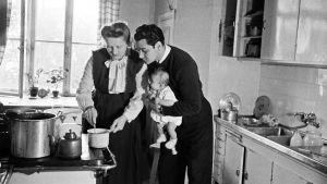 Familj kokar mat i gammalt kök. Kanske 50-tal