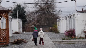 Två skolflickor går på en gång mellan tillfälliga bostadsbaracker