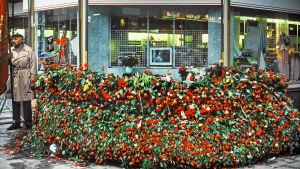 En samtida bild från platsen för Palmemordet med en stor hög av röda rosor på trottoaren.
