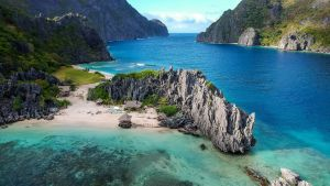 Kuvassa on eksoottinen merimaisema, jossa on vuoria, hiekkaranta ja pieniä bungalowin näköisiä rakennuksia.