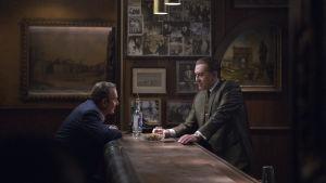 Russel Bufalino (Joe Pesci) och Frank Sheeran (Robert de Niro) sitter och står mittemot varandra vid en öde bardisk.