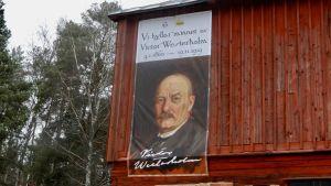 En väggboning föreställande en man med mustasch. Väggboningen är uppsatt på sidan av ett rött hus.