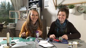 Lee Esselström och Salla Heikkilä istuvat pöydän ääressä ja tekevät käsitöitä