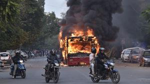 Bild på några motorcyklister som kör förbi en brinnande buss i New Delhi.