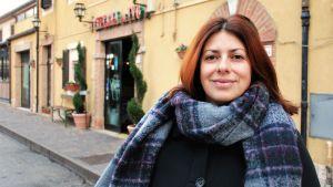 Kvinna med rutig halsduk ser in i kameran och ler. I bakgrunden finns en gul restaurang.