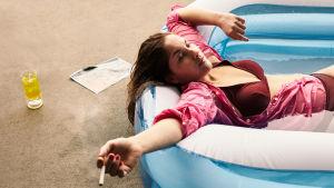 En ung kvinna i rosa skjorta ligger bakåtlutad i en gummibassäng med en cigarett i handen.