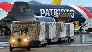 Skyddsutrustning från Kina lastas från plan på Bostons flygplats.