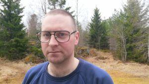 Glasögon prydd man poserar i rural miljö.