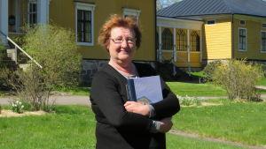 En kvinna med rött hår, glasögon och svart tröja håller om en bok. I bakgrunden ett stort gult hus. Vår, slutet av maj. Soligt.