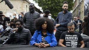 Tre personer håller presskonferens, två står i bakgrunden.