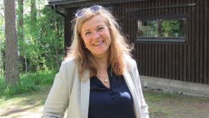 En kvinna med långt hår och solglasögon i hårfästet ler mot kameran. Hon har läppstift, blå skjorta och gråbeige linnekavaj. Hon ser glad ut. I bakgrunden en brun garagebyggnad eller egentligen ett hus.