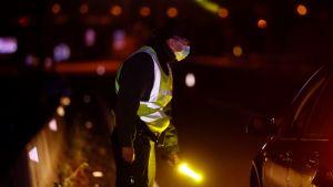 En polisman i skyddsdräkt bredvid en stoppad bil