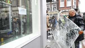 En man flyttar en söndrig fönsterruta.