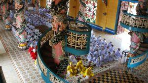 Religionsutövare sitter i rader på golvet i ett vietnamesiskt tempel.