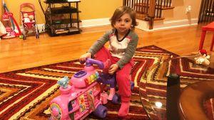 Tvååriga Elyana kör sin leksaksmoped hemma i vardagsrummet i Philadelphia.