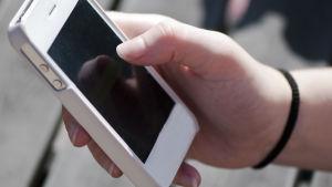 En hand håller i en mobiltlefon.