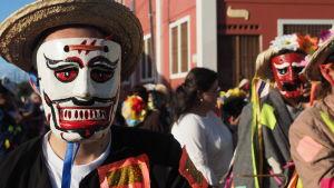En man i vit-röd mask i förgrunden med karnevalgäster i bakgrunden.