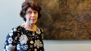 kvinna står framför en brun tavla