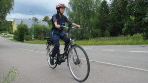 Kvinna cyklar på asfalterad väg.