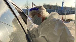Laboratorieskötare gör coronatest vid en bil.