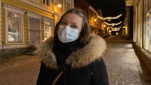 Ann-Sofie står i Borgå gamla stad iklädd vinterjacka och munskydd.