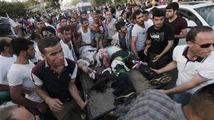 Sårade bärs bort efter attentat mot valmöte i Diyarbakır i östra Turkiet.