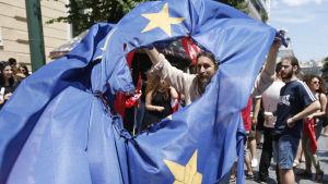 Personer som stöder ett nej till EU:s lånevillkor bränner en EU-flagga i Aten.