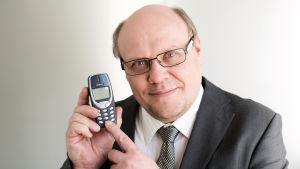 Hannu-Pekka Björkman osoittaa Nokian 3310-puhelinta ja hymyilee kameralle.