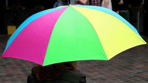 En person håller i ett paraply med ljusblå, lila, grön och gul färg.