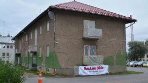 Aravahuset före väggmålningen. Brungrått rappat hus.