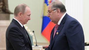 Vladimir Putin och  Alisher Usmanov skakar hand.