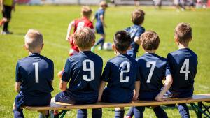 jalkapallojuniorit katsovat peliä vaihtopenkiltä