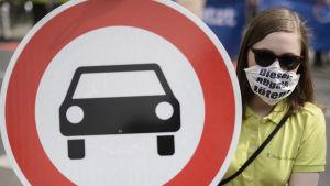 """En kvinna med en ansiktsmask där det står """"diesel-avgas dödar""""  håller upp ett trafikmärke med en bil på."""