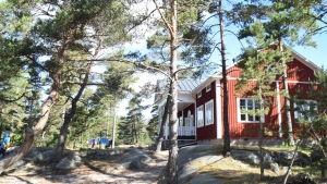 En bild på ett rött hus som står i en skog. skogen består av berg och tallar.